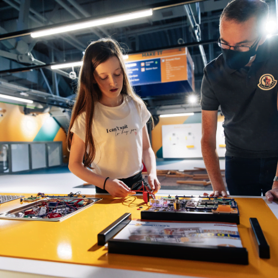 Man looking at circuits exhibit with a child